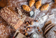 在面包店、静物画用微型新月形面包,面包、牛奶、坚果和面粉 库存照片