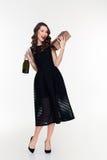 拿着瓶香槟和礼物的可爱的闪光的妇女 库存图片