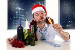 圣诞老人帽子的醉酒的愉快的商人有在新年多士的酒精瓶的与香槟玻璃 免版税库存图片