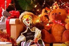 玩具和礼物在圣诞树和文本圣诞快乐下 免版税库存图片