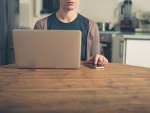 有膝上型计算机和巧妙的电话的妇女在厨房里 免版税图库摄影