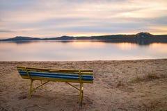 五颜六色的秋天晚上 在海滩的空的长木凳湖 免版税库存图片