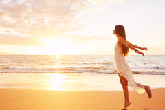 在海滩的愉快的无忧无虑的妇女跳舞在日落 免版税库存图片