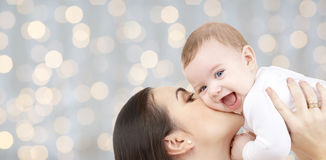 Ευτυχής μητέρα που φιλά το μωρό της πέρα από τα φω'τα Στοκ Φωτογραφίες