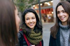 笑三名年轻美丽的妇女画象谈话和 库存图片