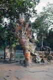 向拿着纳卡语或龙尾巴的被雕刻的恶魔图象扔石头 免版税库存照片