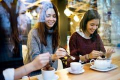 喝咖啡的三名年轻美丽的妇女在咖啡馆商店 免版税库存照片