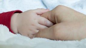 握婴孩手的父亲 图库摄影