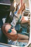 获得愉快的妇女在汽车里面的乐趣 免版税库存照片