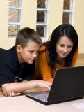 男孩少年膝上型计算机的母亲 免版税图库摄影
