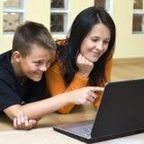 男孩少年膝上型计算机的母亲 免版税库存照片