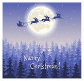 在爬犁的圣诞老人飞行在反对一个神仙的森林的天空 免版税库存照片