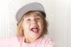 盖帽的滑稽的笑的逗人喜爱的白种人白肤金发的女婴 免版税图库摄影
