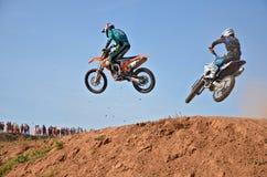 两个参加者摩托车越野赛飞行在小山 免版税库存图片