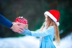 Λατρευτό μικρό κορίτσι που δίνει το δώρο κιβωτίων Χριστουγέννων μέσα Στοκ Φωτογραφία
