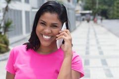 美国本地人妇女讲话在电话在城市 免版税图库摄影