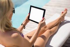 使用片剂计算机的妇女,当坐在轻便折叠躺椅由水池时 免版税库存照片
