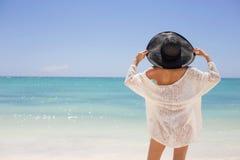 夏天帽子的妇女在海滩 免版税库存照片