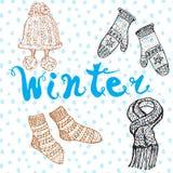 冬天季节集合乱画元素 与温暖的衣裳的手拉的集合、袜子和帽子和字法词 免版税图库摄影