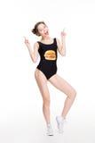 设计师游泳衣的愉快的女性指向用两只手的 免版税库存照片