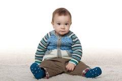时尚男婴坐白色地毯 免版税库存照片