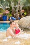 教他的小孩女儿的活跃父亲游泳在热带手段的水池 免版税库存照片
