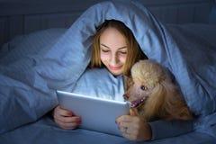 在床上的女孩与片剂 免版税库存照片