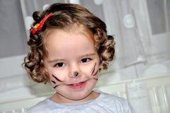 有面孔的逗人喜爱的小女孩被绘象猫 免版税库存图片