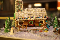 糖果和椒盐脆饼在圣诞节的原木小屋 库存照片