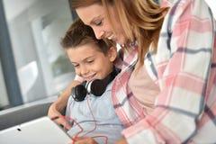 照顾和她在家使用片剂的微笑的儿子 免版税库存照片