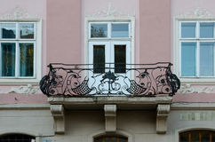 窗口和桃红色墙壁背景的葡萄酒开放加工铁阳台  免版税库存图片