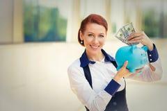 愉快的成功的年轻女商人放置的金钱美元在存钱罐中 库存照片