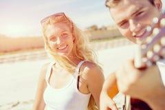 Молодые пары играя гитару на пляже в влюбленности Стоковое Фото