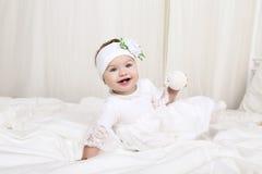 白色衣裳的逗人喜爱的矮小的女婴,坐床,使用与玩具 图库摄影
