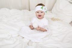 白色衣裳的逗人喜爱的矮小的女婴,坐床,使用与玩具 库存图片
