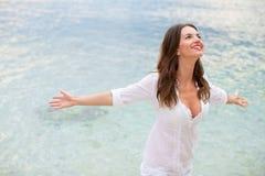 放松在与胳膊的海滩的妇女打开享受她的自由 免版税库存照片