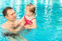 教他的小孩女儿的活跃父亲游泳在热带手段的水池 库存图片