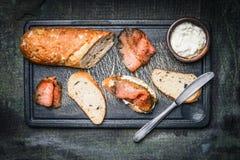 与三文鱼、乳清干酪和长方形宝石的快餐三明治在土气背景 免版税图库摄影