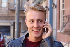 Κλείστε τον ελκυστικό νέο τύπο επάνω χαμόγελου που μιλά σε κάποιο χρησιμοποιώντας το κινητό τηλέφωνο Στοκ εικόνα με δικαίωμα ελεύθερης χρήσης