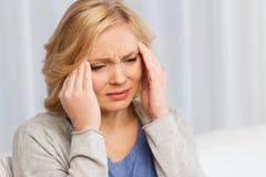 在家遭受头疼的不快乐的妇女 免版税库存图片