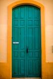 在黄色墙壁的绿色门 库存照片