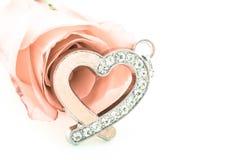 金刚石心脏与桃红色玫瑰的形状垂饰 库存图片