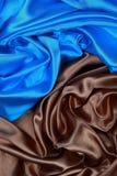 波浪折叠蓝色和棕色丝绸缎布料构造背景 免版税库存图片
