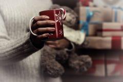 在手中杯和堆礼物 库存图片