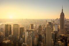 与都市摩天大楼的纽约地平线柔和的日出的 库存图片