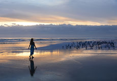 Женщина ослабляя на пляже на восходе солнца Стоковые Фото