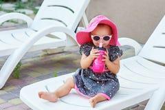 Λίγο κοριτσάκι στα ποτά πάρκων φθινοπώρου από το ρόδινο πλαστικό μπουκάλι Στοκ Εικόνες