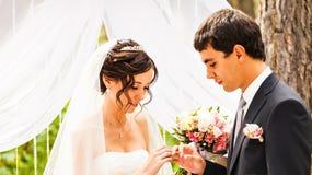 Γλιστρώντας δαχτυλίδι νεόνυμφων στο δάχτυλο της νύφης στο γάμο Στοκ Εικόνα