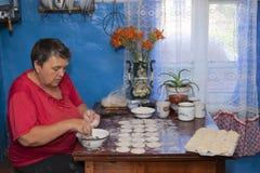 妇女在家庭厨房里烹调饺子 免版税库存图片