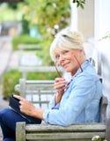 资深户外妇女阅读书画象  库存图片